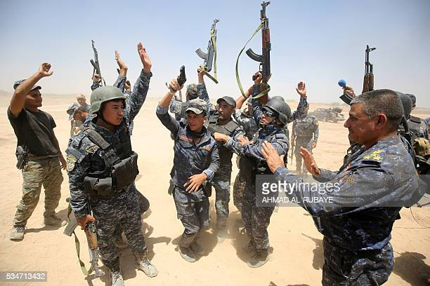 Pro-government forces fighters celebrate in the al-Sejar village, in Iraq's Anbar province, on May 27 as they take part in a major assault to retake...