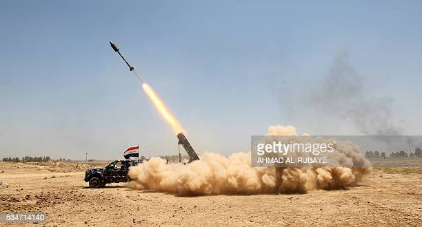 Pro-government forces fighters fire a rocket in the al-Sejar village, in Iraq's Anbar province, on May 27 as they take part in a major assault to...