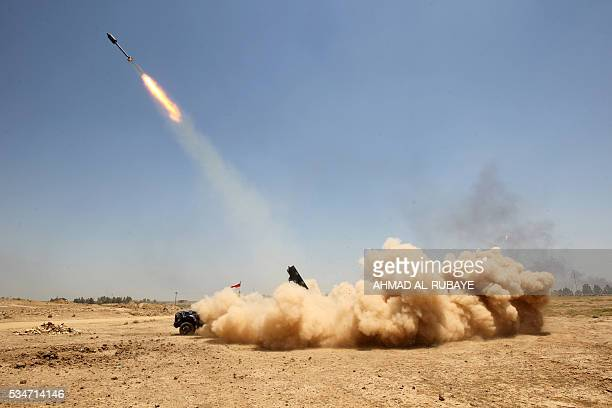 Progovernment forces fighters fire a rocket in the alSejar village in Iraq's Anbar province on May 27 as they take part in a major assault to retake...