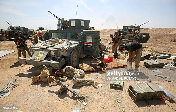 Progovernment forces fighters rest after battling Islamic State group jihadists near alSejar village in Iraq's Anbar province on May 26 as they take...