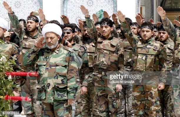 Progovernment forces gesture during a funeral ceremony in the Sayyida Zeinab mosque on the outskirts of Damascus on April 26 for the victims of a...