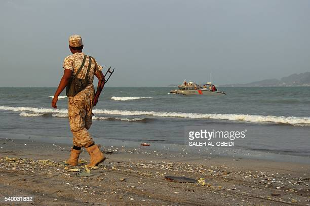 A progovernment forces soldier walks along the beach in the southern coastal city of Aden as Yemeni coast guards search for the remains of a United...
