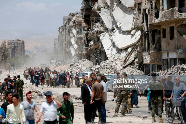 TOPSHOT Progovernment forces stand in the destroyed Thalateen Street in the Yarmuk Palestinian refugee camp on the southern outskirts of the capital...
