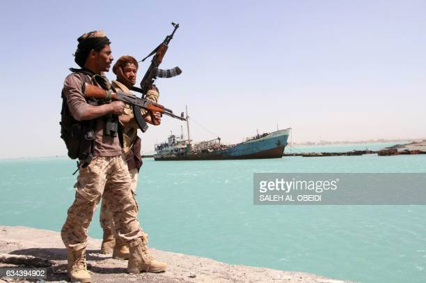 Progovernment forces walk in the port of the western Yemeni coastal town of Mokha as they advance in a bid to try to drive the Shiite Huthi rebels...