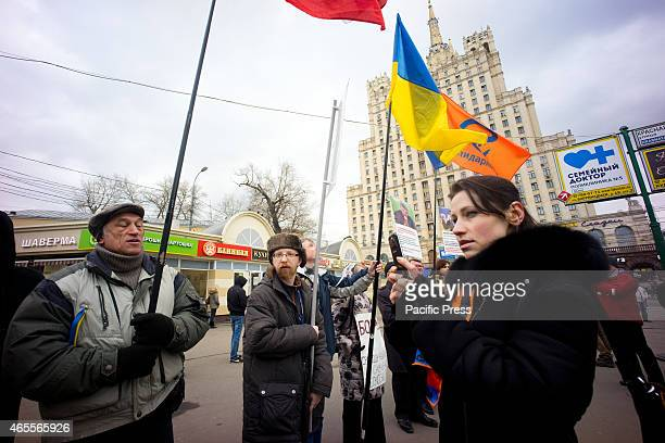 A progovernment lady wearing the St George ribbon recording the antiwar rally using her mobile phone A group of AntiWar in Ukraine activists held a...