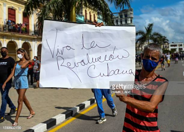 """Progovernment man holds a signal that reads """"Long live the Cuban revolution"""" during a protest against the government of Cuban President Miguel..."""