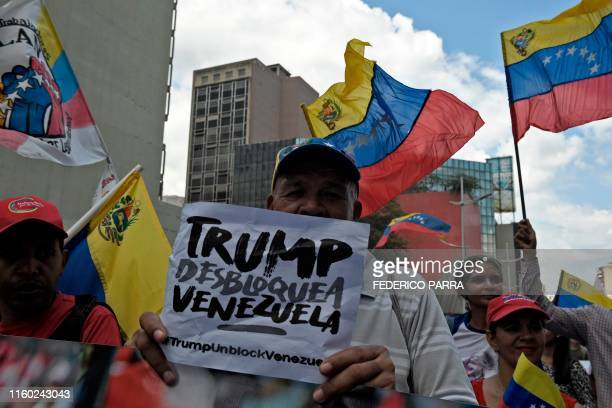 A progovernment protester rallies against US sanctions with a sign reading Trump unblock Venezuela in Caracas on August 7 2019 Washington warned...