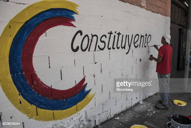 A progovernment supporter paints a mural on a wall at Andres Bello high school which will be used as a polling station in Caracas Venezuela on...