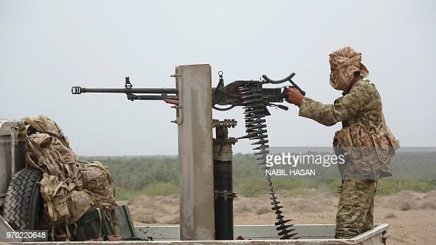 A Progovernment Yemeni soldier fires a machine gun on June 7 near the city of Al Jah in the Hodeida province 50 kilometres from the port city of...