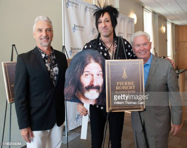 Program Director Bill Weston and General Manager Joe Bell pose for a photo with air personality Jacky Bam Bam as he holds an oversized picture of...