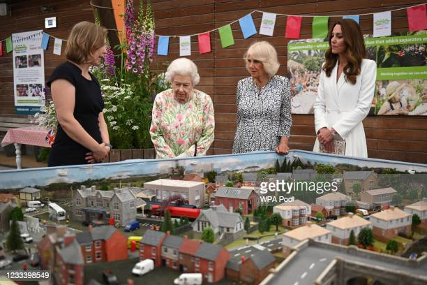 Programme Director at Eden Project, Lindsey Brummitt shows a scale model of Big Lunch events that have been held over the years to Queen Elizabeth II...