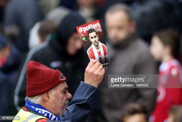 A programme seller sells the match programme to fans in the stands