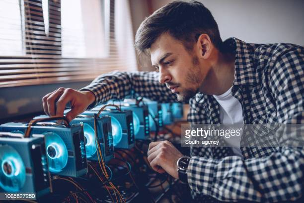programmer preparing mining rig - financial technology stock photos and pictures