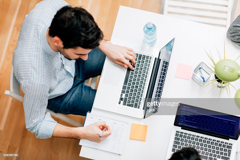 Programmer working in his office : Stock Photo