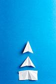 Progress concept. Development attainment, motivation, growth concept. Business concept of goals, success, achievement and challenge. White paper airplanes under construction on blue background.