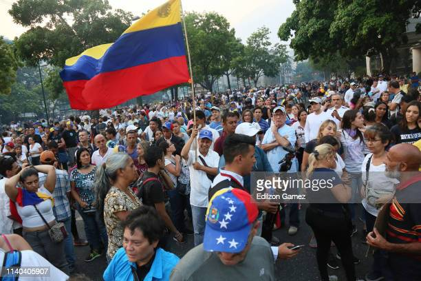 Pro-Guaidó demonstrator holds a flag of Venezuela during clashes with Pro-Government military police officers near La Carlota air force on April 30,...