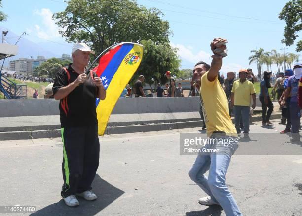 A proGuaidó demonstrator throws rocks to military forces near La Carlota air force on April 30 2019 in Caracas Venezuela Through a live broadcast via...