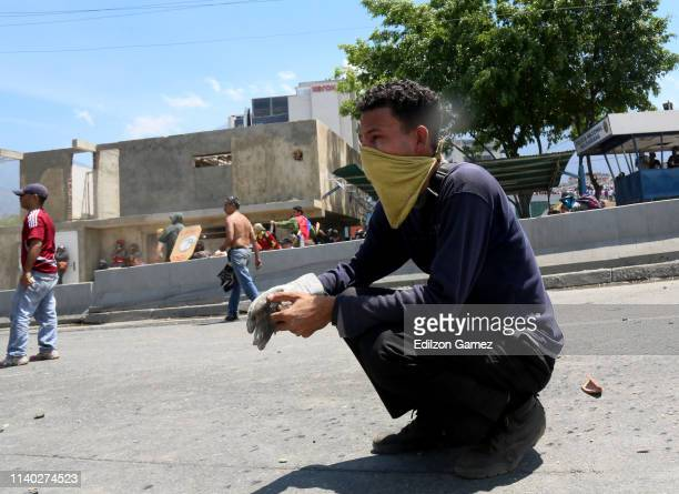 A proGuaidó demonstrator with his face covered takes a rock to throw to military forces near La Carlota air force on April 30 2019 in Caracas...