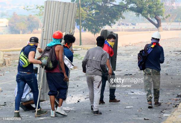 ProGuaidó demonstrators clash with ProGovernment military police officers near La Carlota air force on April 30 2019 in Caracas Venezuela Through a...
