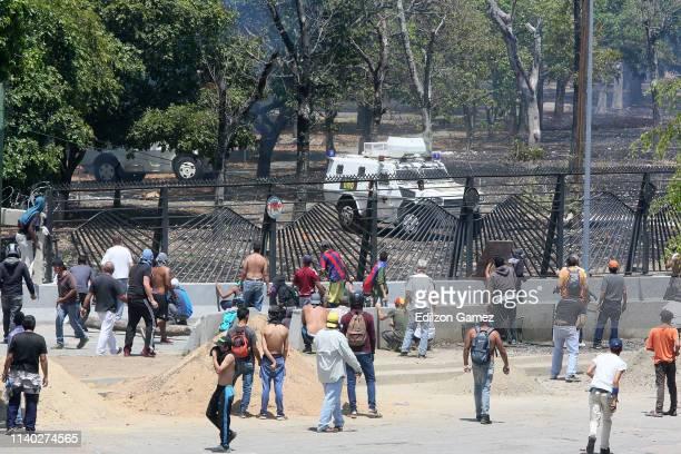 ProGuaidó demonstrators throw rocks to military forces near La Carlota air force on April 30 2019 in Caracas Venezuela Through a live broadcast via...