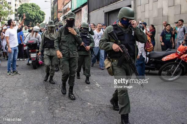 ProGuaidó police officers walk around Altamira distribuitor on April 30 2019 in Caracas Venezuela Through a live broadcast via social media...