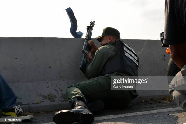 ProGuaidó soldier protects himself behind a wall as he hold a machine gun outside the air force base La Carlota on April 30 2019 in Caracas Venezuela...