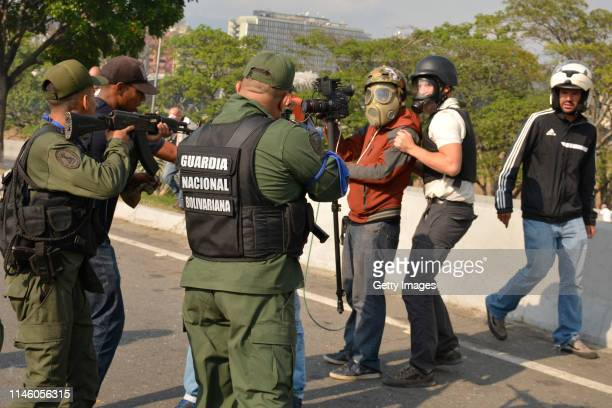 Pro-Guaidó soldiers point their weapons towards a cameraman in the outskirts of the air force base La Carlota on April 30, 2019 in Caracas,...