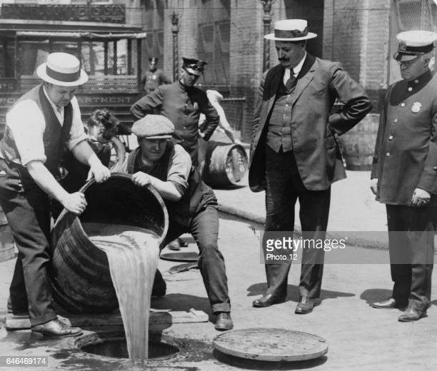 A barrel of confiscated illegal beer being poured down a drain