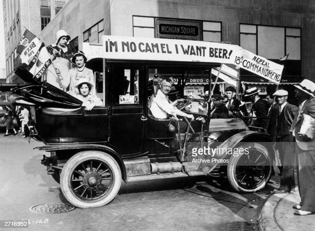 Prohibition protesters parade in a car emblazoned with signs and flags calling for the repeal of the 18th Amendment One sign reads 'I'M NO CAMEL I...