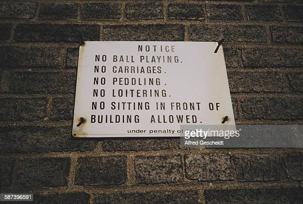 A prohibitive sign in New York City 1993 It reads 'Notice No Ball Playing No Carriages No Peddling No LoiteringNo Sitting in Front of Building...