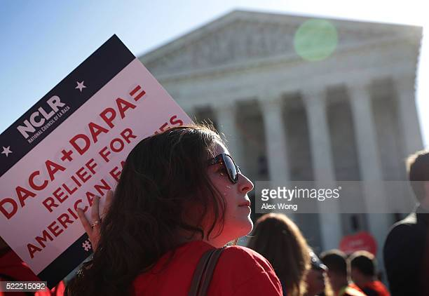 A proimmigration activist holds a sign in front of the US Supreme Court on April 18 2016 in Washington DC The Supreme Court is scheduled to hear oral...