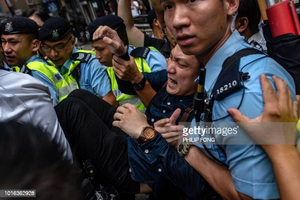 Proindependence activist Wayne Chan is removed by police from a location outside the Foreign Correspondents' Club as people protest ahead of a speech...