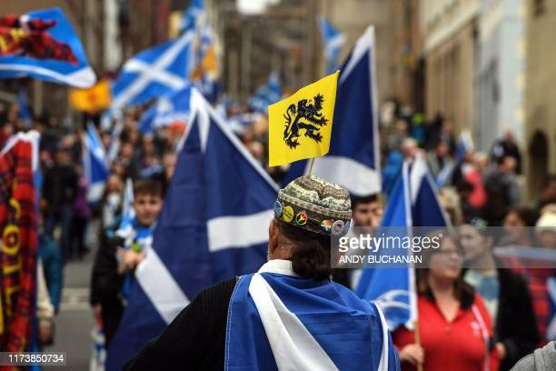 Pro-independence activists wave Scottish Saltire flags as they march from Holyrood to the Meadows in Edinburgh, Scotland on October 5, 2019. -...