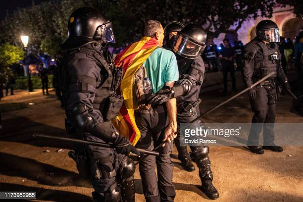 Pro-independence demonstrator argues with Catalan police officers, Mossos d'Esquadra, as they clear the main entrance of the Parliament of Catalonia...