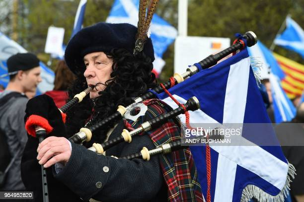 A proindependence demonstrator with Saltire flags the national flag of Scotland plays the bagpipes after a march in support of Scottish independence...