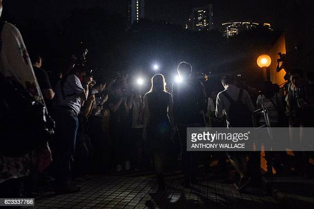 Proindependence lawmakers Baggio Leung and Yau Waiching are surrounded by members of the press as they leave the High Court after holding a press...
