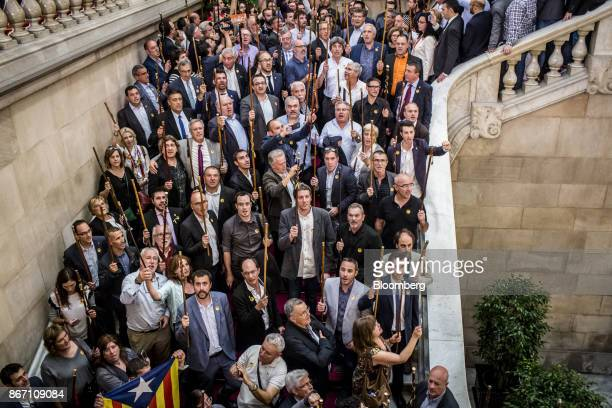 Proindependence mayors raise their batons and sing the Catalan anthem following a vote in favour of independence at the Catalan parliament in...