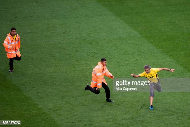 A proindependence of Catalonia protestor jumps onto the pitch during the La Liga match between Barcelona and Las Palmas at Camp Nou on October 1 2017...