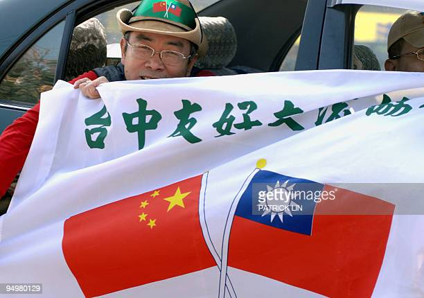 A proindependence protester holds a banner printed with the national flags of Taiwan and China to satirize the closer TaipeiBeijing economic ties...