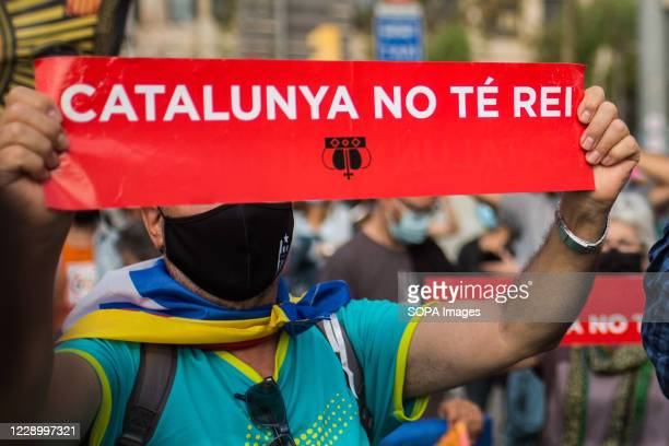 Pro-independence protester wearing a face mask while holding a placard saying 'Catalonia there is no king' during the demonstration. Anti-monarchical...