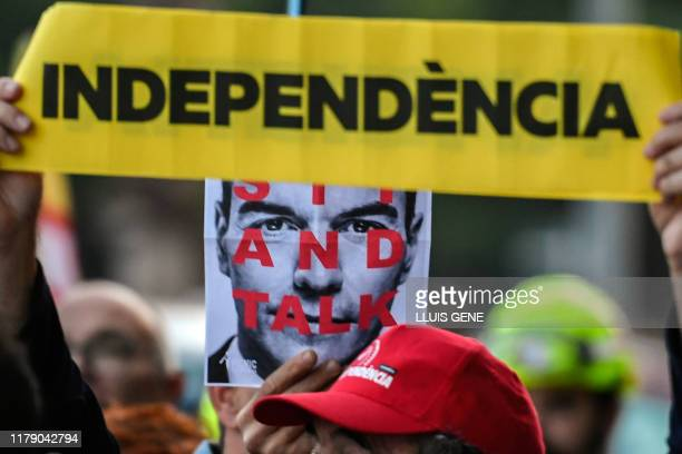 """Pro-independence protesters hold placards depicting Spanish Prime Minister Pedro Sanchez with the words """"sit and talk"""" next to another one reading..."""