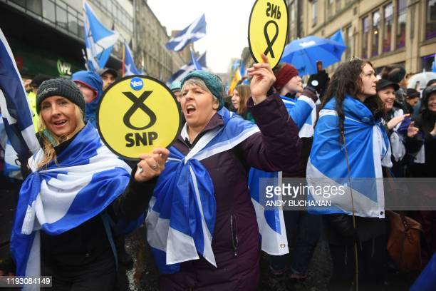 Pro-independence protesters hold up Scottish National Party emblems as they join a march organised by the grassroots organistaion All Under One...