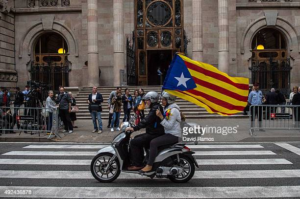 ProIndependence supporters hold up a ProIndependence Catalan flag as they drive past the main entrance of the Catalonia High Court as Catalonia's...
