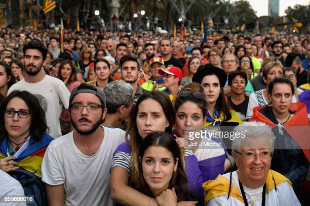 Proindependence supporters react as they watch on broadcast screens outside the Parliament of Catalunya as the Catalan President Carles Puigdemont...