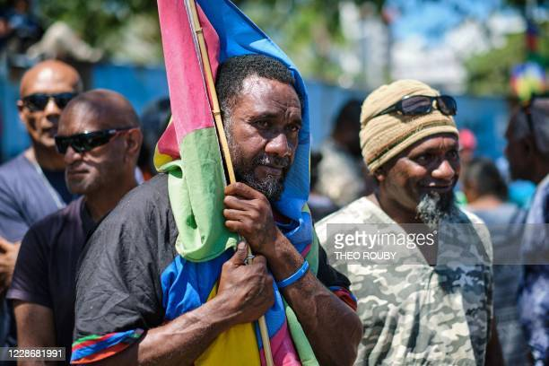 A proindependence sympathizer protects himself from the sun with a flag of the Socialist Kanak National Liberation Front as he takes part in a...