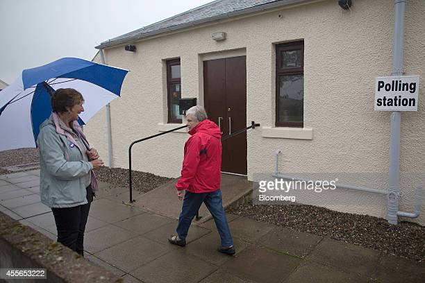 A proindependence 'yes' campaigner shelters from the rain beneath a blue and white umbrella as a voter a arrives at a polling station to cast her...
