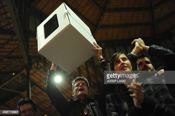 A Proindependentis man holds a urn during a meeting organised by the Catalonia National Assembly and the Omnium Cultural civil society association...