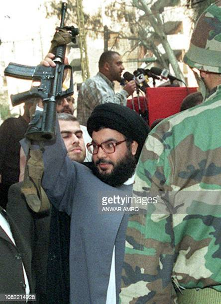 ProIranian Hezbollah Secretary General Hassan Nasrallah brandishes an Israeli machinegun offered to him by a Hezbollah militant 17 May 1999 during a...