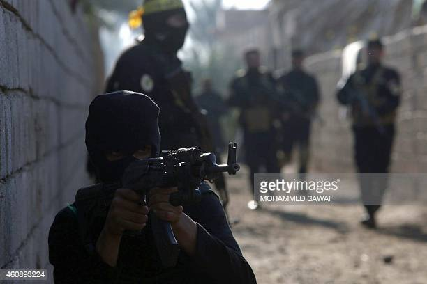 ProIraqi government fighters some belonging to the Iraqi Imam Ali Brigade take part in an operation to secure an area they seized from the Islamic...