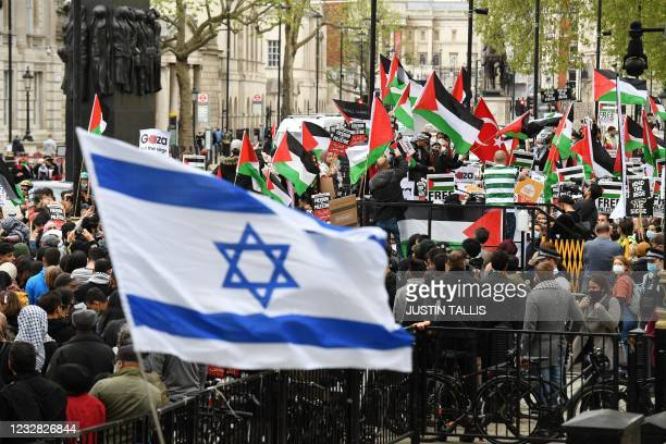 Pro-Israel activists wave an Israeli flag as pro-Palestinian activists take part in a demonstration protesting against Israeli attacks on...